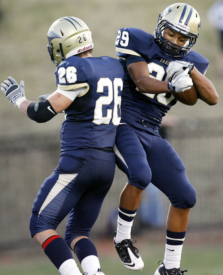 Photo - Southmoore's Johnathan Martin (right) celebrates a touchdown by Andrew Long (left) during their high school football game at Moore Stadium in Moore, Oklahoma on Friday, September 9, 2011. Photo by John Clanton, The Oklahoman