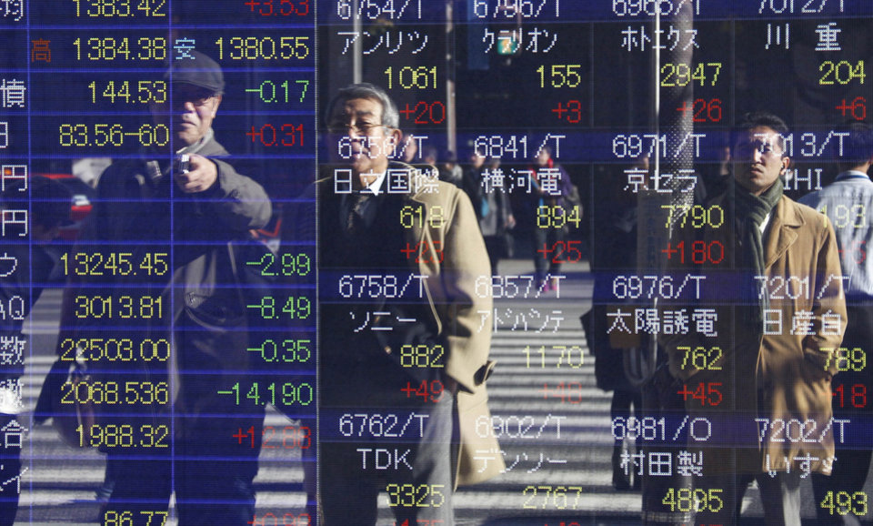 Photo - People are reflected on the electronic board of a securities firm in Tokyo Thursday, Dec. 13, 2012. Asian stock markets rose Thursday with the help of Japan's Nikkei 225, which was propelled higher by a weakening yen. (AP Photo/Koji Sasahara)