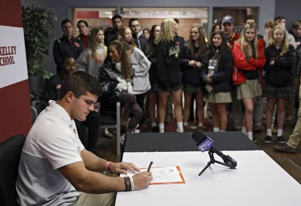 Photo -  Running back Zach Middleton signs to play football at Oklahoma State during a signing day ceremony at Tulsa Kelley in December. [Mike Simons/Tulsa World]