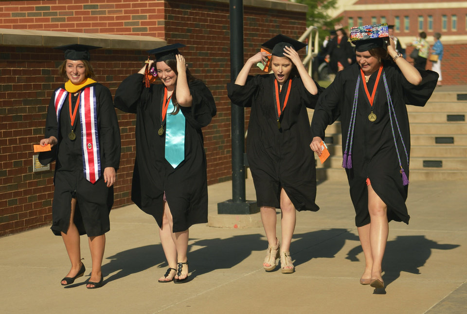New graduates McCall Wilson (right), Morgan Crank, Lindsey Gray and Jenna Elizabeth walk to Oklahoma State's commencement ceremony held in Gallagher Iba Arena on May 10, 2014. Photo by Jackie Dobson for the Oklahoman