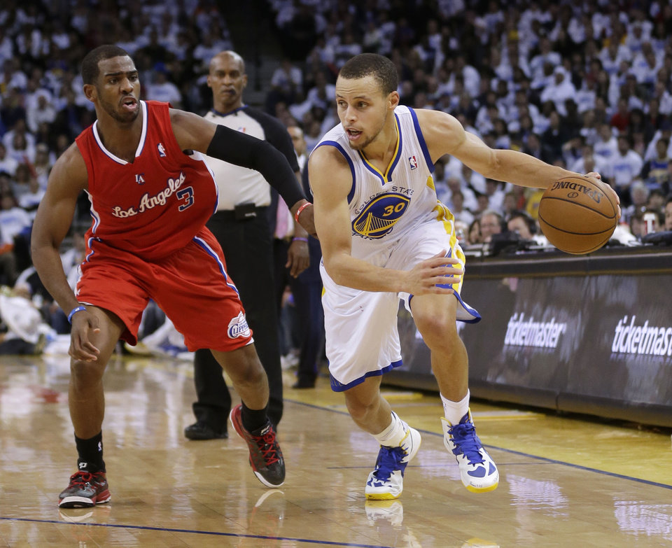 Photo - Golden State Warriors' Stephen Curry (30) dribbles past Los Angeles Clippers' Chris Paul (3) during the second half of an NBA basketball game in Oakland, Calif., Wednesday, Jan. 2, 2013. Golden State won 115-94. (AP Photo/Marcio Jose Sanchez)