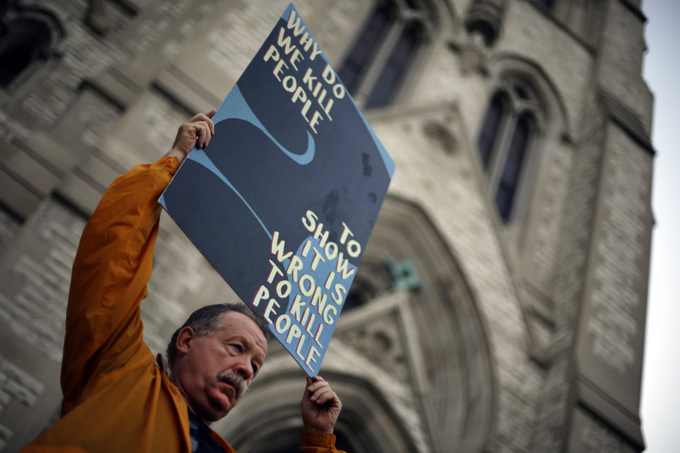Photo - Death penalty opponent Herve Deschamps holds a sign over his head during a vigil outside St. Francis Xavier College Church hours before the scheduled execution of Missouri death row inmate Russell Bucklew, Tuesday, May 20, 2014, in St. Louis. A federal appeals court panel granted a temporary halt to the execution of Bucklew on Tuesday evening citing concerns that he could suffer during lethal injection due to a rare medical condition. The panel's ruling could be overturned by the full appeals court, or by the U.S. Supreme Court. (AP Photo/Jeff Roberson)