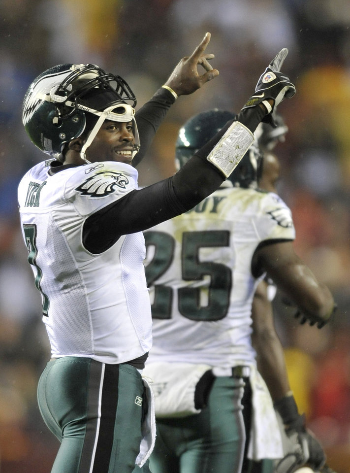 Photo - FILE - In a Nov. 15, 2010 file photo, Philadelphia Eagles quarterback Michael Vick celebrates after throwing a touchdown pass to wide receiver Jeremy Macli during the first half of an NFL football game against the Washington Redskins, in Landover, Md. The New York Jets signed quarterback Michael Vick and released Mark Sanchez on Friday, March 21, 2014. Vick was a free agent after spending the last five seasons with the Phialdelphia Eagles. (AP Photo/Gail Burton, File)