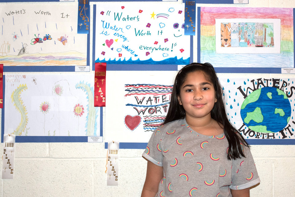 Photo -  Mahi Gahlot, 9, poses in front of her drawing (top row, middle) that won second place at the 2018 Water's Worth It art show. [PHOTO BY WHITNEY BRYEN, FOR THE OKLAHOMAN]