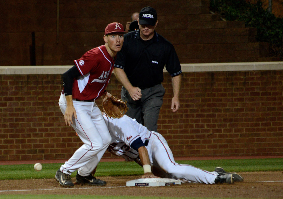 Photo - Virginia's Mike Papi, front right, makes it to third as Arkansas' Bobby Wernes, left, looks back at second baseman Brian Anderson after a bad throw during the third inning of an NCAA college baseball regional tournament game in Charlottesville, Va., Saturday, May 31, 2014. (AP Photo/Pat Jarrett)