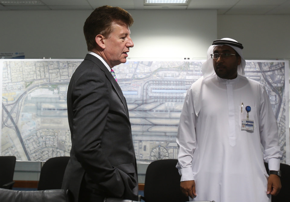 Photo - In this June 17, 2014, photo, Dubai Airports CEO Paul Griffiths, left, a 56-year-old Briton, talks with one of his Emirati staff while he is visiting the Joint Control Room which is essentially the nerve center of operations for the airport in Dubai, United Arab Emirates. Now that he's had a taste of running the world's busiest air hub for international passengers, Griffiths is determined to hang on to the honor while setting his sights on an even bigger prize: beating Atlanta for the title of busiest airport on the planet. (AP Photo/Kamran Jebreili)