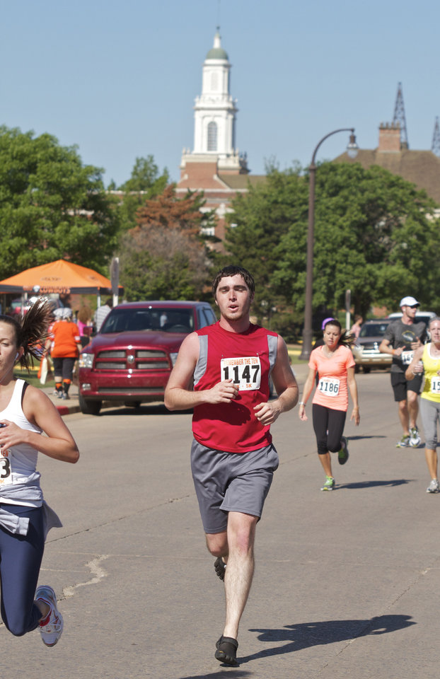 Bryson Kinder runs in front of the OSU Library Steeple during The Remember the Ten run held in Stillwater, Okla., on April 21, 2012. Photo by Mitchell Alcala, for the Oklahoman