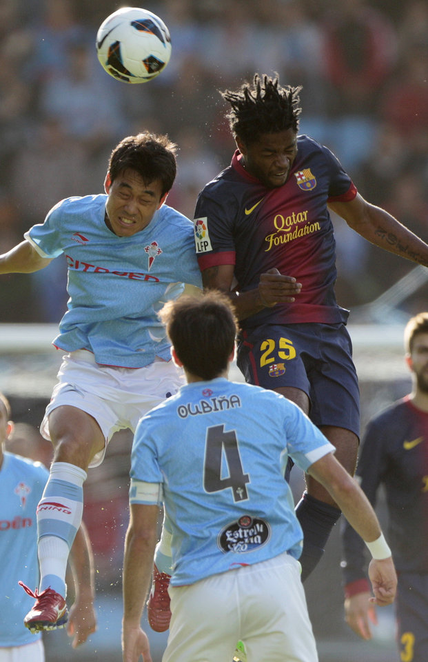 RC Celta\'s Park Chu-Young from South Korea, left, challenges for the ball with FC Barcelona\'s Alex Song from Cameroon, right, during a Spanish La Liga soccer match at the Balaidos stadium in Vigo, Spain, Saturday, March 30, 2013. (AP Photo/Lalo R. Villar)