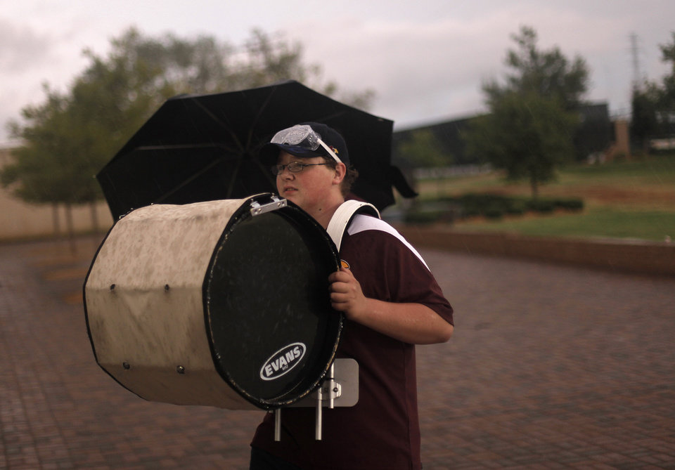 Photo - Andrew Ringer, a sophomore at Clinton High School, carries his drum out of the rain before a high school football game between Heritage Hall and Clinton in Oklahoma City, Friday, Sept. 7, 2012.  The game was delayed due to lightning.  Photo by Garett Fisbeck, The Oklahoman