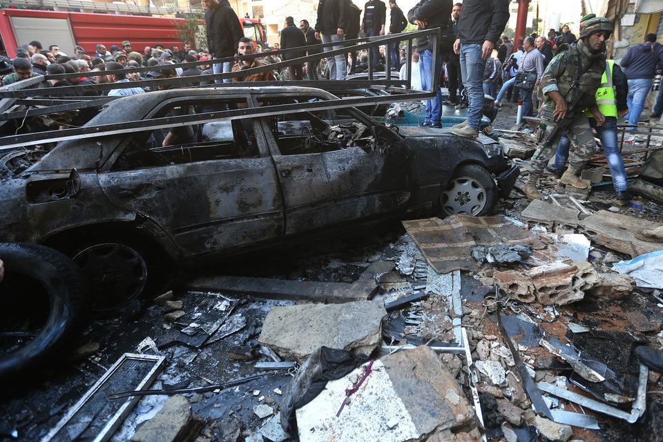 Photo - A Lebanese army soldier walks through the site of a car bombing in the southern suburb of Beirut, Lebanon, Tuesday, Jan. 21, 2014. A car bomb ripped through a Shiite neighborhood in southern Beirut killing several people and setting plumes of smoke over the area in the latest attack targeting supporters of the militant Hezbollah group in Lebanon. (AP Photo/Hussein Malla)