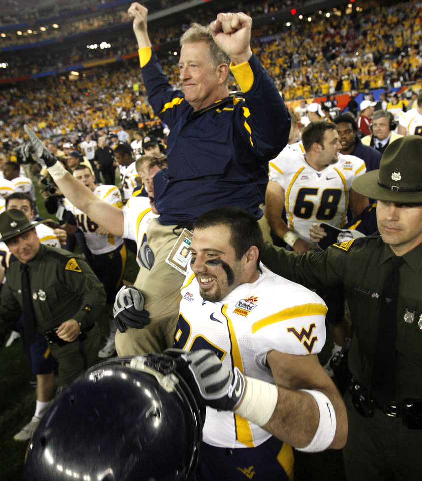 Photo - CARRY: West Virginia head coach Bill Stewart is carried to the center of the field at the end of the Fiesta Bowl college football game between the University of Oklahoma Sooners (OU) and the West Virginia University Mountaineers (WVU) at The University of Phoenix Stadium on Wednesday, Jan. 2, 2008, in Glendale, Ariz.   BY STEVE SISNEY, THE OKLAHOMAN ORG XMIT: KOD