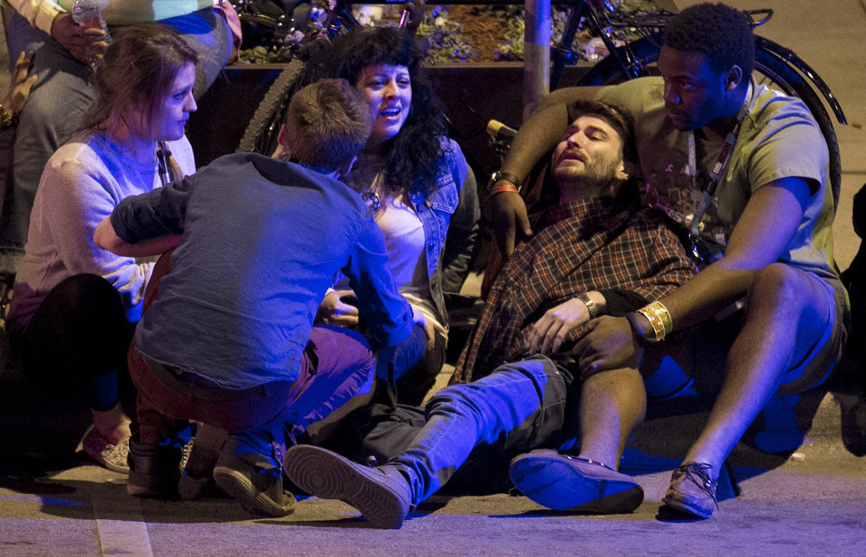 Photo - Unidentified people are comforted after being struck by a vehicle on Red River Street in downtown Austin, Texas, during SXSW on Wednesday March 12, 2014. Police say two people were confirmed dead at the scene after a car drove through temporary barricades set up for the South By Southwest festival and struck a crowd of pedestrians.  (AP Photo/Austin American-Statesman, Jay Janner)
