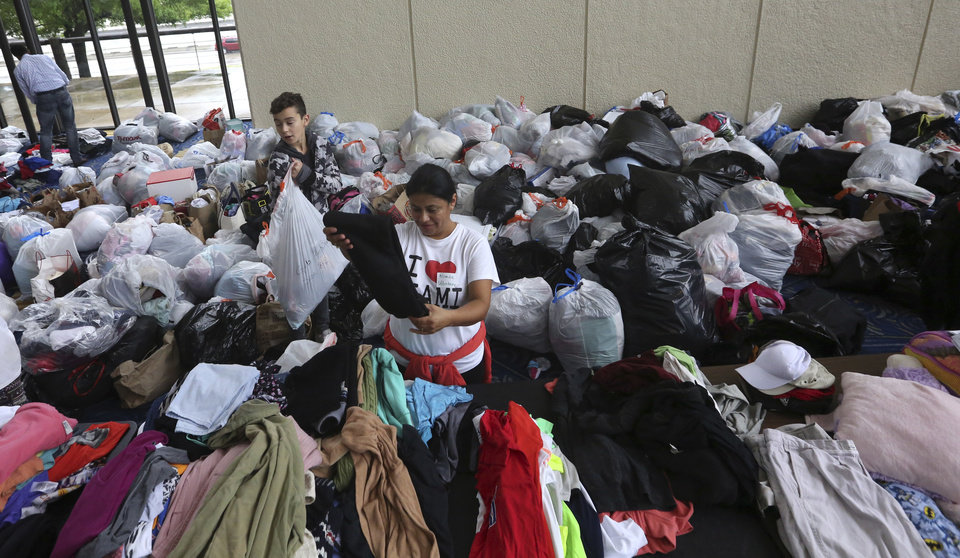 Photo - Volunteers Brenda Tcoc, right, and Hugo Wilson help sort bags of donated clothes for victims of the flooding from Tropical Storm Harvey after a shelter opened at the Lakewood Church in Houston, Texas, Tuesday, Aug. 29, 2017. (AP Photo/LM Otero)