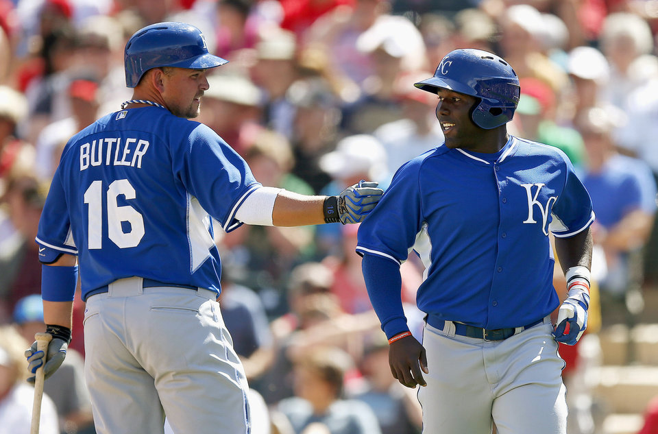 Photo - Kansas City Royals' Billy Butler (16) gives teammate Edinson Rincon a slap on the shoulder after Rincon scored against the Los Angeles Angels during the second inning of a spring training baseball game Friday, March 21, 2014, in Tempe, Ariz. (AP Photo/Ross D. Franklin)