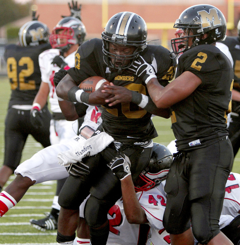 Photo - Midwest City's James Flanders, left, scores a touchdown beside Myles Hogg as Del City's Quintrell Boykins tries to bring him down during a high school football game in Midwest City, Okla., Friday, September 3, 2010.  Photo by Bryan Terry, The Oklahoman