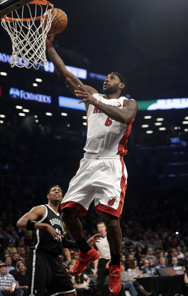 Photo - Miami Heat's LeBron James (6) drives past Brooklyn Nets' Paul Pierce (34) during the first half of an NBA basketball game on Friday, Jan. 10, 2014, in New York. (AP Photo/Frank Franklin II)