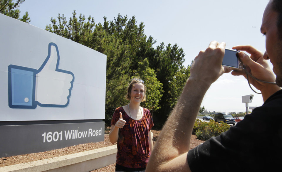 Photo -   German tourists who use Facebook, take pictures outside of Facebook headquarters in Menlo Park, Calif., Friday, Aug. 17, 2012. Facebook stock is trading at $19 and has lost half its market value since its May public offering. (AP Photo/Paul Sakuma)