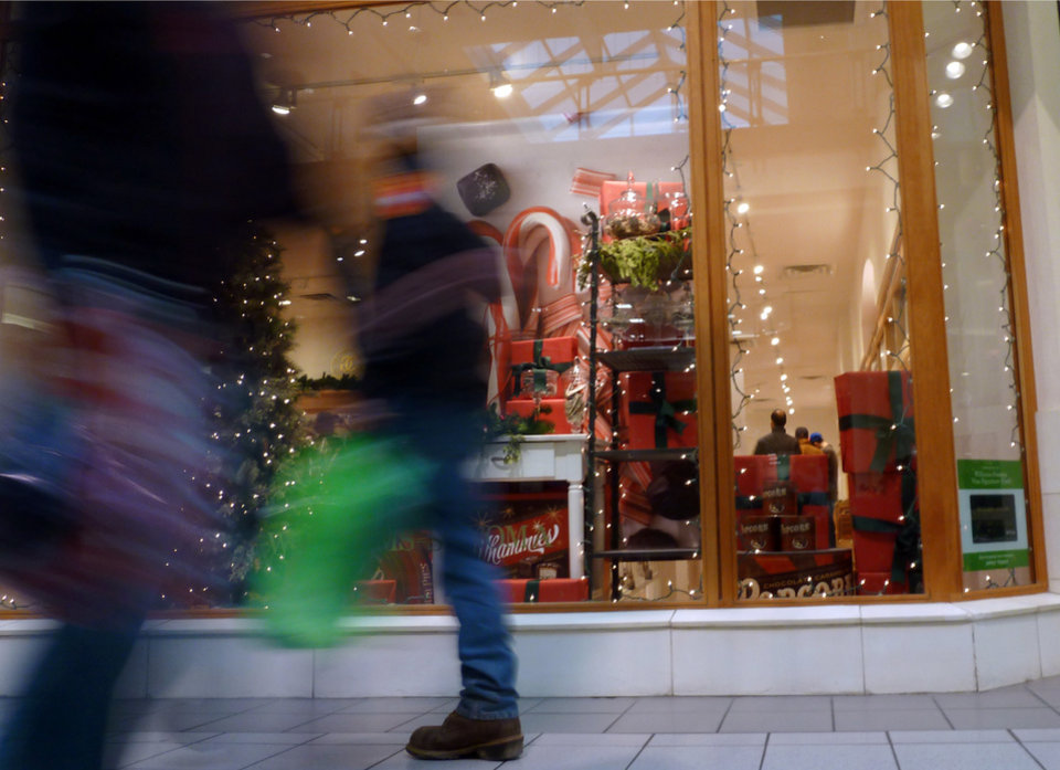 In this Friday, Dec. 21, 2012, photo, shoppers walk past a store at a mall in Salem, N.H. U.S. consumer confidence tumbled in December, driven lower by fears of sharp tax increases and government spending cuts set to take effect next week. The Conference Board said Thursday that its consumer confidence index fell this month to 65.1, down from 71.5 in November. That's second straight decline and the lowest level since August. (AP Photo/Elise Amendola)