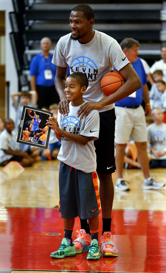 Photo - Mason Lee, 10, gets a picture made with Kevin Durant during Durant's basketball camp on Thursday, Aug. 7, 2014 in Moore, Okla. Photo by Steve Sisney, The Oklahoman