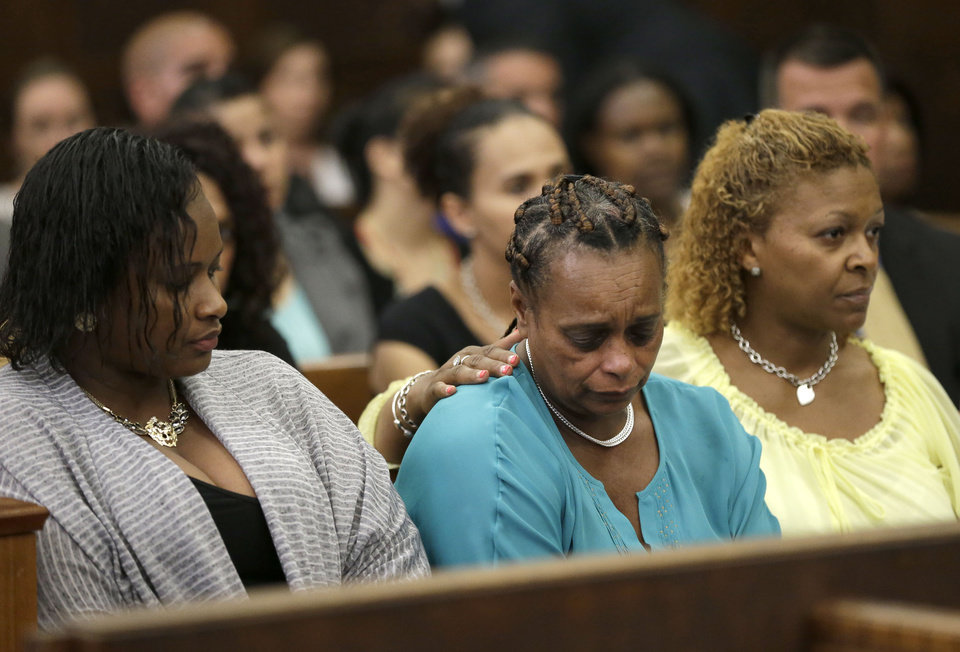 Photo - Women identified by the assistant clerk of the court as a victim's family members support one another during a hearing for former New England Patriots football player AaronHernandez in Suffolk Superior Court, Tuesday, June 24, 2014, in Boston.  Prosecutors allege that Hernandez ambushed and shot to death two men, Daniel de Abreu and Safiro Furtado, in 2012 after a chance encounter inside a Boston nightclub. Hernandez has pleaded not guilty. (AP Photo/Steven Senne, Pool)