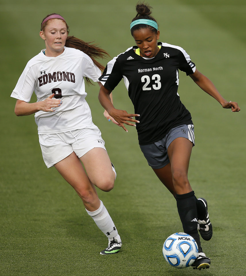 Photo - Norman North's Haley Woodard goes past Edmond Memorial's Baye Mayberry on her way to scoring during the Class 6A girls soccer championship between Edmond Memorial and Norman North in Norman, Okla., Friday, May 16, 2014. Photo by Bryan Terry, The Oklahoman