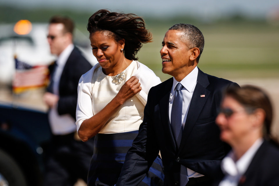 Photo - President Barack Obama and first lady Michelle Obama walk to greet supporters on the tarmac after landing aboard Air Force One at Austin-Bergstrom International Airport, in Austin, Texas, Thursday, April 10, 2014. The president and first lady traveled to the University of Texas at Austin to attend the Civil Rights Summit, a conference commemorating the 50th anniversary of the 1964 Civil Rights Act. (AP Photo/ Tamir Kalifa)