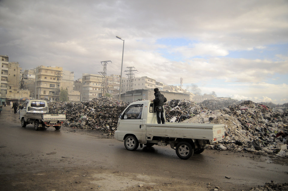 Photo -   In this Saturday, Nov. 10, 2012 photo, trucks pass a mountain of garbage in a roundabout in Aleppo, Syria. Due the heavy fighting and shelling, the garbage collection system collapsed weeks ago. (AP Photo/Mónica G. Prieto)