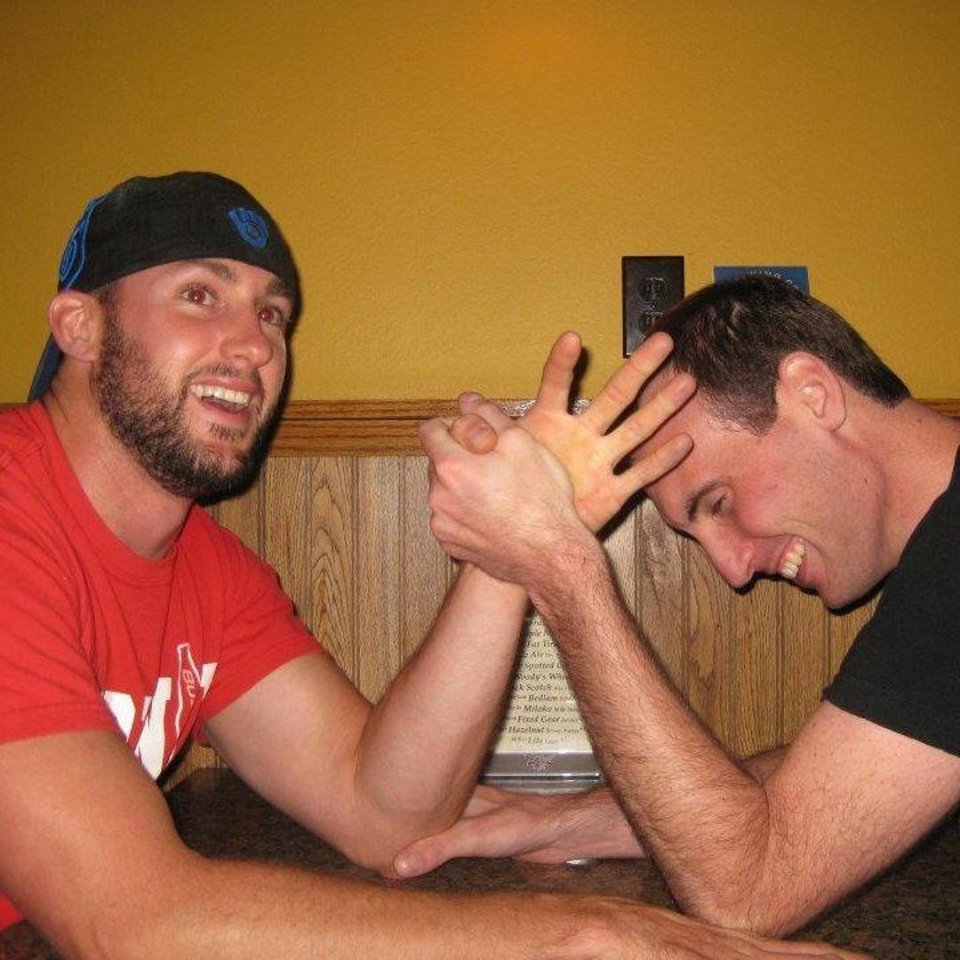 Photo - In this 2012 photo provided by Joseph Kindred, Justin Lentz, left, 32, and Jarrard Law, 34, both of Portage, Wis., arm wrestle. Relatives say the two men were skiing Saturday, Feb. 15, 2014, near Leadville, Colo., when they were killed in an avalanche that also left three others with moderate injuries. (AP Photo/Joseph Kindred)