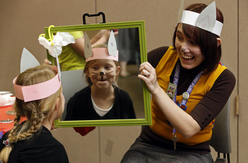 Children's librarian Heather Fellenstein shows Natalie Rich, 6, the results of her face-painting efforts.