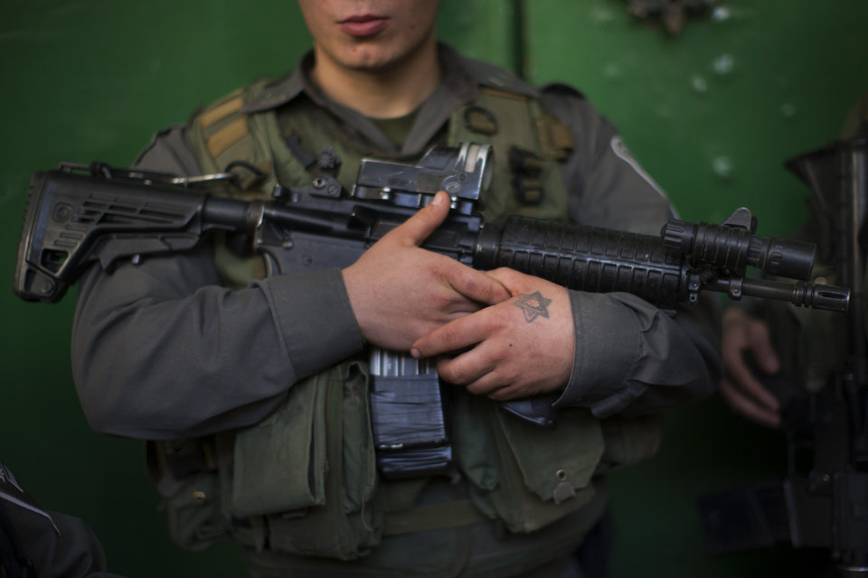 Photo - An Israeli border police guards a door inside the site known to Jews as the Tomb of the Patriarchs, and to Muslims as the Ibrahimi Mosque, in the West Bank city of Hebron, Monday, Jan. 14, 2013. (AP Photo/Bernat Armangue)