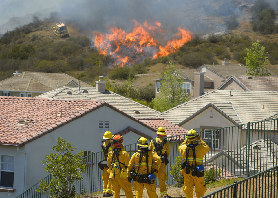 Photo - Firefighters from Glendale, Calif., and Pasadena, Calif., stand watch as bulldozers clear a firebreak near a wildfire burning along a hillside near homes in Thousand Oaks, Calif., Thursday, May 2, 2013. A Ventura County Fire Department spokeswoman said the blaze that broke out Thursday morning near Camarillo and Thousand Oaks, 50 miles west of Los Angeles, had spread to over 6,500 acres, forcing evacuations of nearby neighborhoods. (AP Photo/Mark J. Terrill)