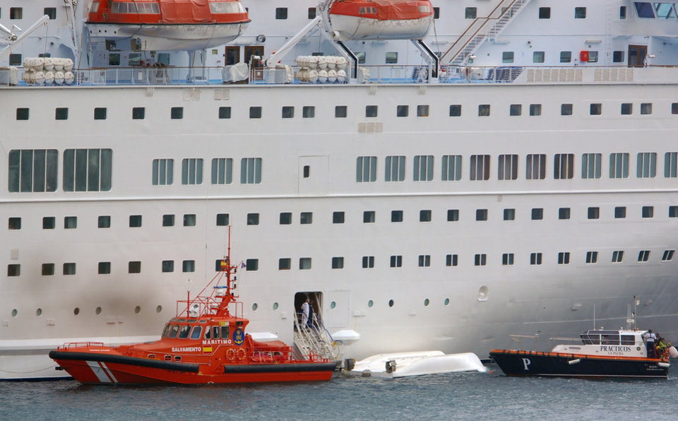 An orange rescue boat docks by a capsized lifeboat from the British-operated cruise ship Thomson Majesty in Santa Cruz port of the Canary Island of La Palma, Spain, Sunday Feb. 10, 2013. A lifeboat from the Thomson Majesty fell into the sea at port in Spain�s Canary Islands, killing five people and injuring three others Sunday, officials said. Rescue personnel were called to the dockside after a lifeboat with occupants had fallen overboard from a cruise ship. Spanish national broadcaster RTVE said an emergency training drill was taking place at the time of the accident. (AP Photo/Manuel Gonzalez)