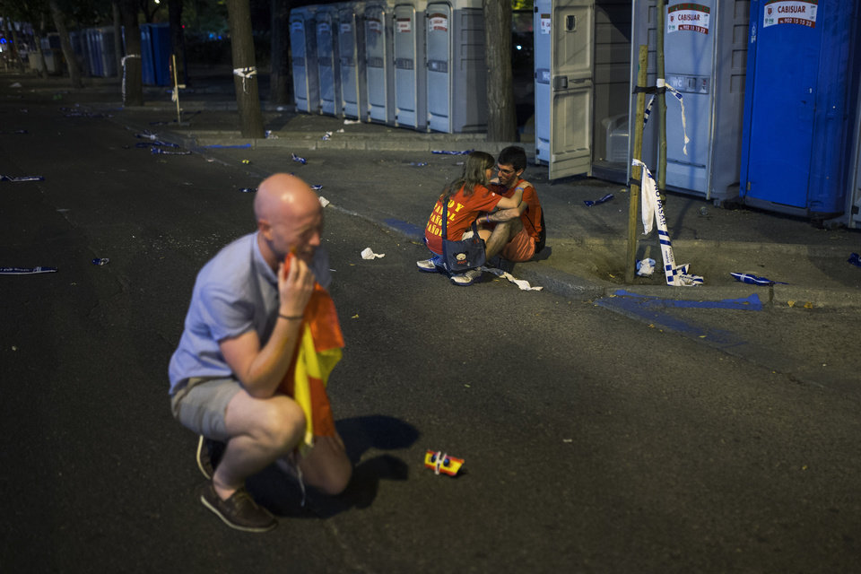 Photo - A British fan, left, and his friends, unseen, joke as a Spanish girl consoles her boyfriend, right, at the fan park after the World Cup soccer match between Spain and Chile, in Madrid, Spain, Wednesday, June 18, 2014. Spain lost the match which knocks them out of the World Cup. (AP Photo/Andres Kudacki)