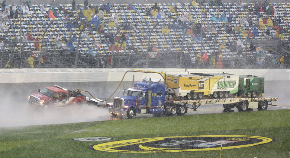 Photo - Track dryers go along the front stretch during a rain delay in the Daytona 500 NASCAR Sprint Cup Series auto race at Daytona International Speedway in Daytona Beach, Fla., Sunday, Feb. 23, 2014. (AP Photo/John Raoux)