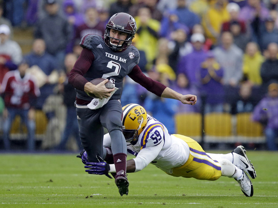 Photo - FILE - In this Nov. 23, 2013, file photo, Texas A&M quarterback Johnny Manziel (2) scrambles to avoid a tackle by LSU defensive end Jermauria Rasco (59) during the first half of an NCAA college football game in Baton Rouge, La. Manziel could be the answer to Cleveland's prayers at quarterback. The polarizing and popular Texas A&M star will likely be available when the Browns pick fourth in next week's NFL draft. But can they handle the Johnny Football Circus? (AP Photo/Gerald Herbert, File)
