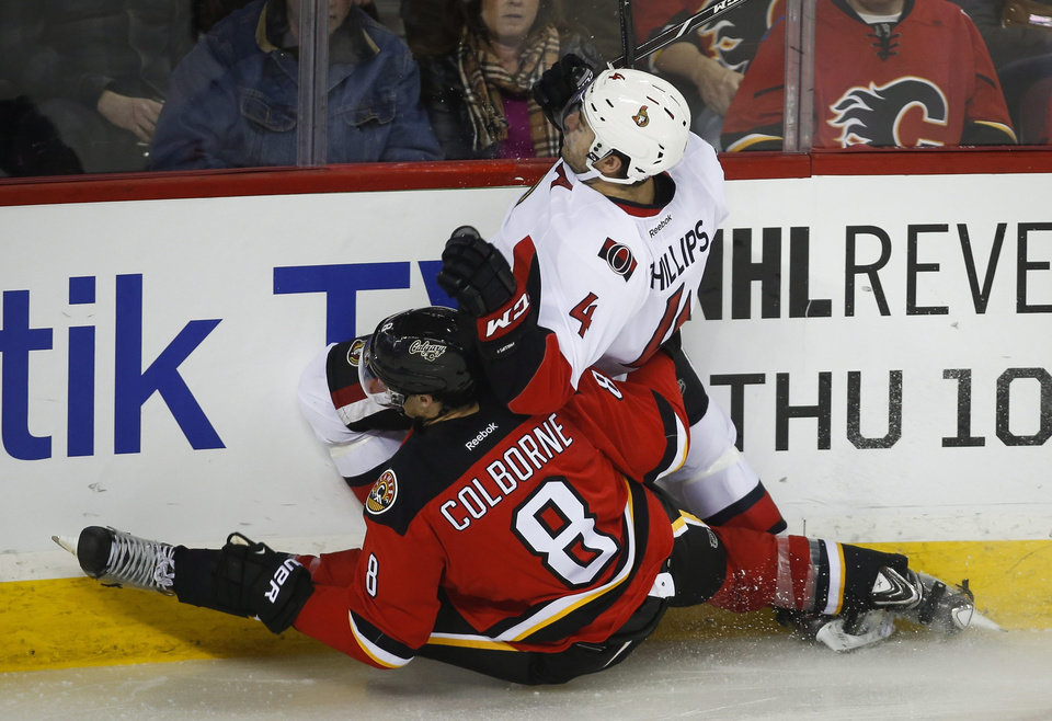 Photo - Ottawa Senators' Chris Phillips, right, gets carried into the boards by Calgary Flames' Joe Colborne during third period NHL hockey action in Calgary, Alberta, Wednesday, March 5, 2014. The Calgary Flames beat the Ottawa Senators 4-1. (AP Photo/The Canadian Press, Jeff McIntosh)