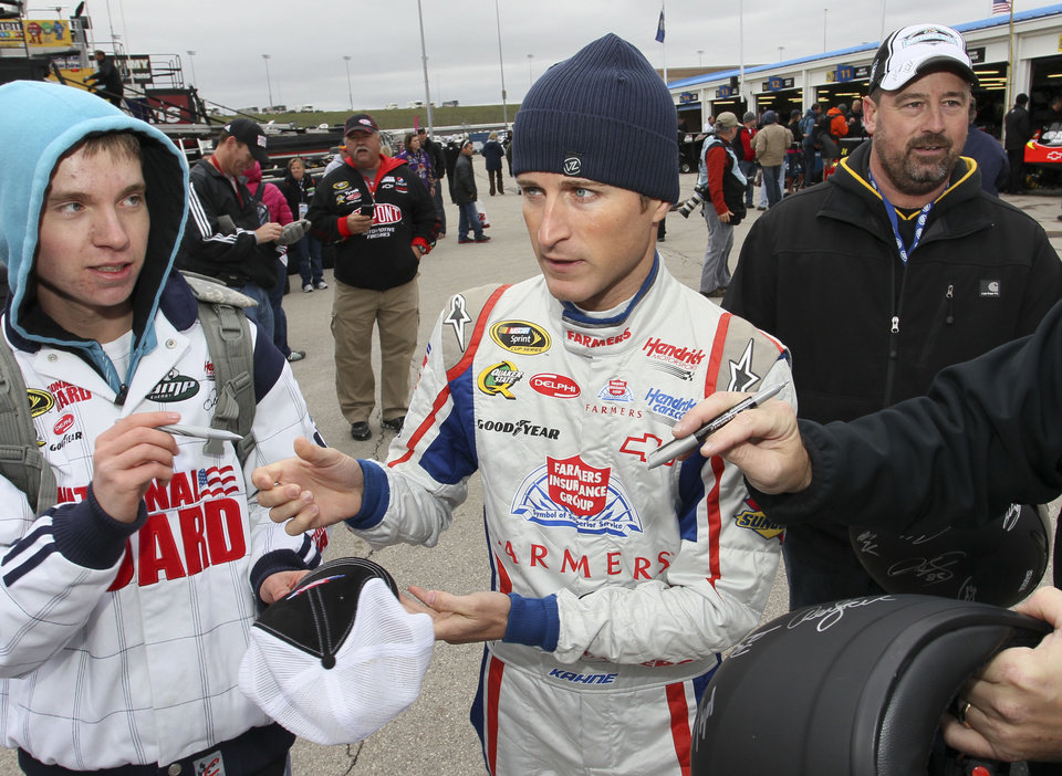 Driver Kasey Kahne signs autographs before practice for the Sunday's NASCAR Sprint Cup Series auto race at Kansas Speedway in Kansas City, Kan., Friday, Oct. 19, 2012. (AP Photo/Colin E. Braley)