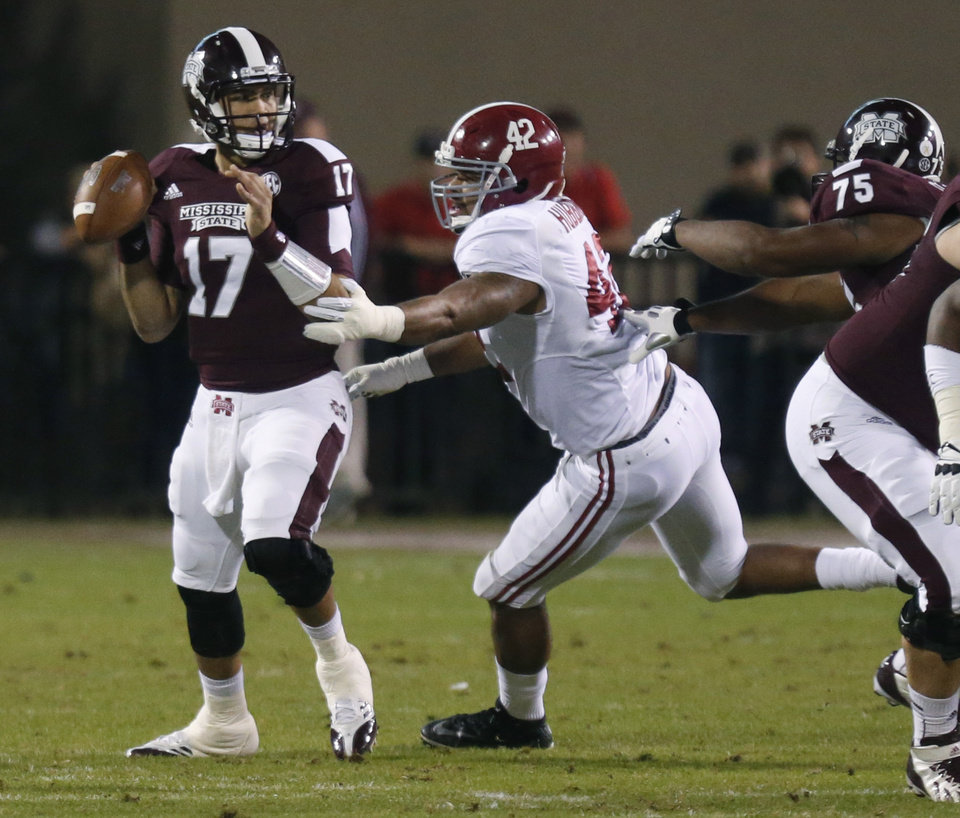 Photo - Mississippi State quarterback Tyler Russell (17) looks for an open receiver as Alabama linebacker Adrian Hubbard (42) closes in during the first half of an NCAA college football game, Saturday, Nov. 16, 2013, in Starkville, Miss. (AP Photo/Rogelio Solis)