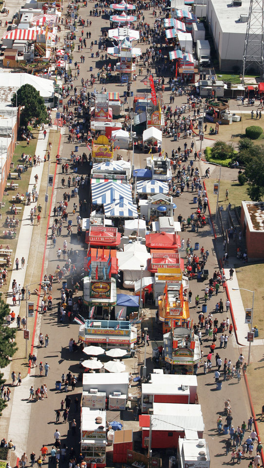 Photo - Crowds fill the midway on a warm sunny afternoon at the Oklahoma State Fair on Saturday. The view is from inside the OGE tower ride.  Photos by Steve Sisney, The Oklahoman
