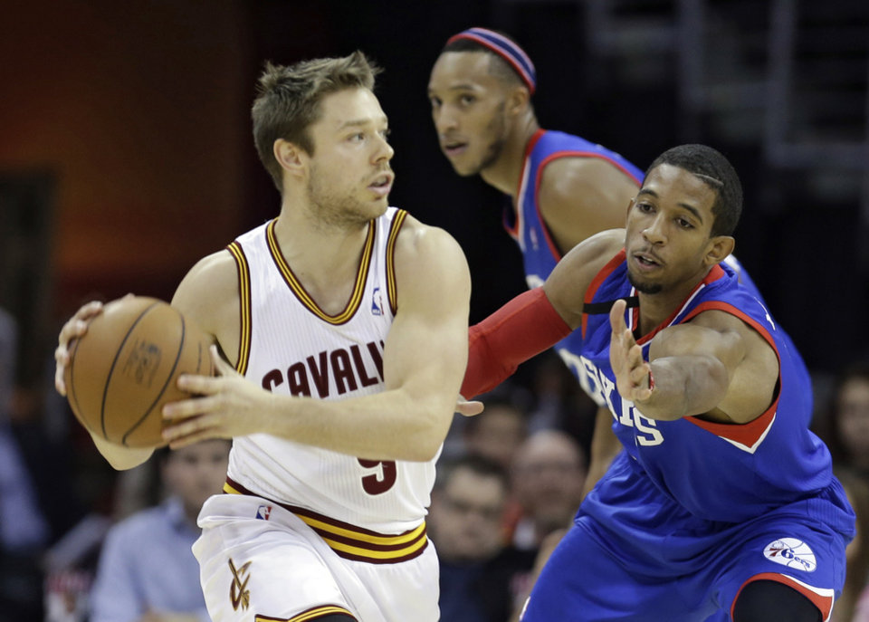 Photo - Cleveland Cavaliers' Matthew Dellavedova, left, from Australia, looks to pass under pressure from Philadelphia 76ers' Darius Morris during the first quarter of an NBA basketball game Saturday, Nov. 9, 2013, in Cleveland. (AP Photo/Tony Dejak)