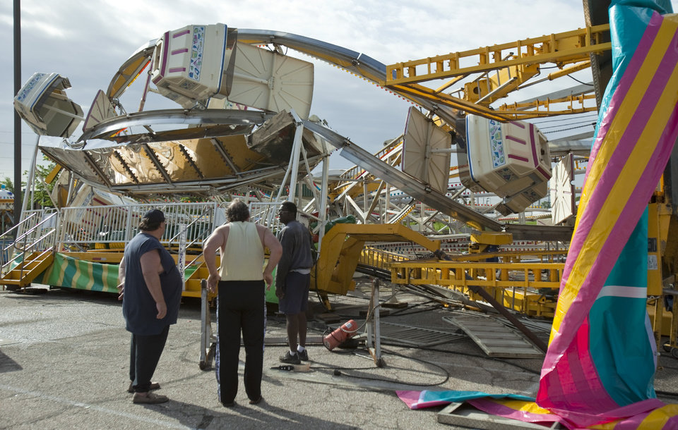 Photo -   Ottaway Amusement, Inc. workers survey the damage to a 65-foot tall Ferris wheel Sunday morning, April 15, 2012, that toppled over onto another ride at Kellogg and Greenwicht following a tornado that swept through east Wichita overnight Saturday. (AP Photo/The Wichita Eagle, Mike Hutmacher)