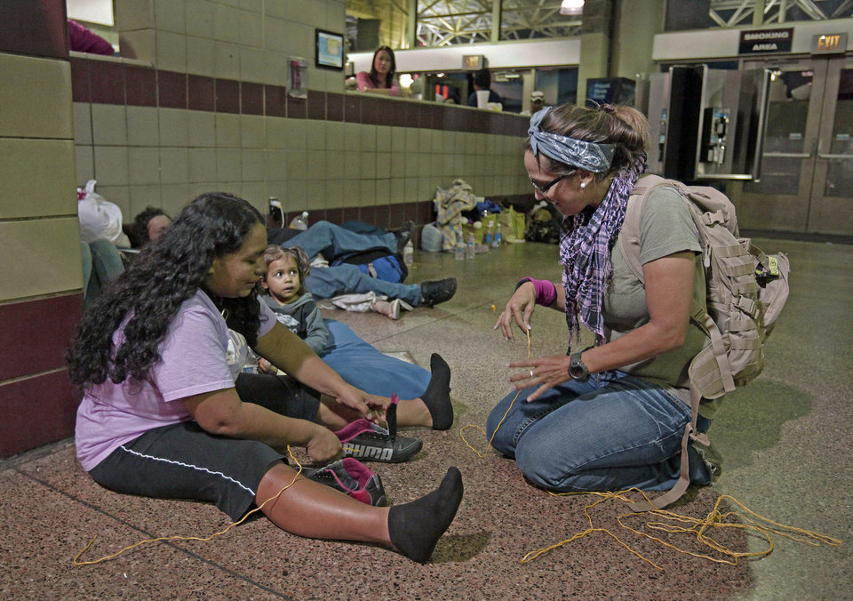 Photo - Volunteer Michelle Lewis of Phoenix, right, helps Doris Suyapa, of Honduras, with her shoes, by using yellow rope for shoe laces, Thursday, May 29, 2014 at the Greyhound bus terminal in Phoenix.  About 400 mostly Central American women and children caught crossing from Mexico into south Texas were flown to Arizona this weekend after border agents there ran out of space and resources.  Officials then dropped hundreds of them off at Phoenix and Tucson Greyhound stations, overwhelming the stations and humanitarian groups who were trying to help. (AP Photo/Rick Scuteri)