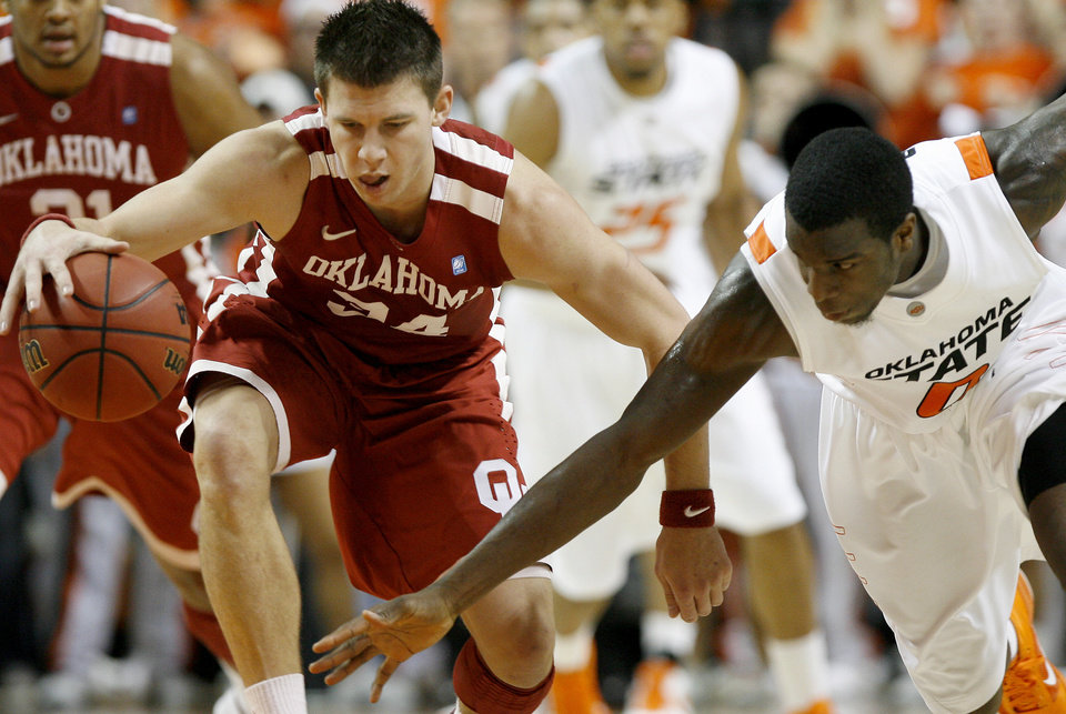 Photo - Oklahoma's Cade Davis (34) gains control of the ball beside Oklahoma State's Jean-Paul Olukemi (0) during the Bedlam men's college basketball game between the University of Oklahoma Sooners and Oklahoma State University Cowboys at Gallagher-Iba Arena in Stillwater, Okla., Saturday, February, 5, 2011. Photo by Bryan Terry, The Oklahoman