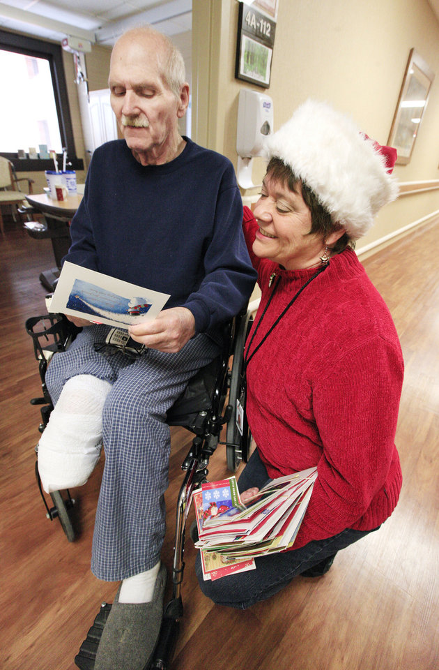 Photo - Veteran Terry DeLaughter, of Midwest City, receives a Christmas card from Sami Clack, regional specialist for Red Cross Service to the Armed Forces, as cards from the Holiday Mail for Heroes program are delivered by the Red Cross at the VA Medical Center.  Photo by Paul B. Southerland, The Oklahoman  PAUL B. SOUTHERLAND - PAUL B. SOUTHERLAND