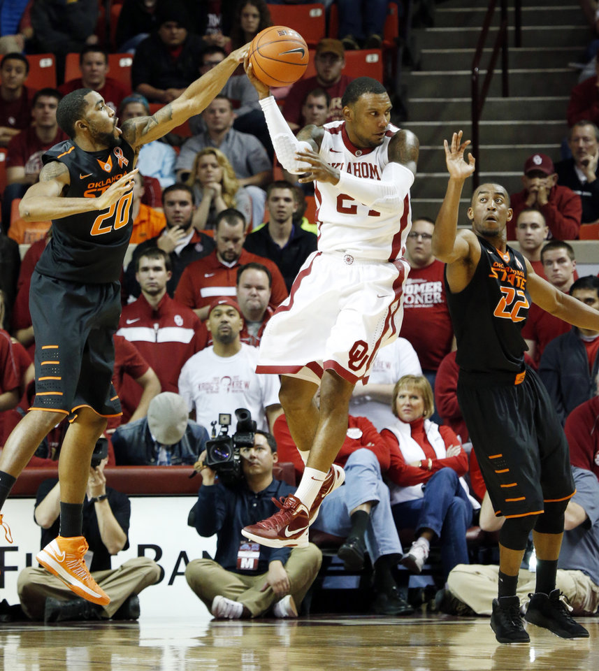 Photo - Sooner's Romero Osby (24) makes a pass from between Cowboy's Michael Cobbins (20) and Markel Brown (22) as the University of Oklahoma Sooners (OU) play the Oklahoma State Cowboys (OSU) in NCAA, men's college basketball at The Lloyd Noble Center on Saturday, Jan. 12, 2013  in Norman, Okla. Photo by Steve Sisney, The Oklahoman
