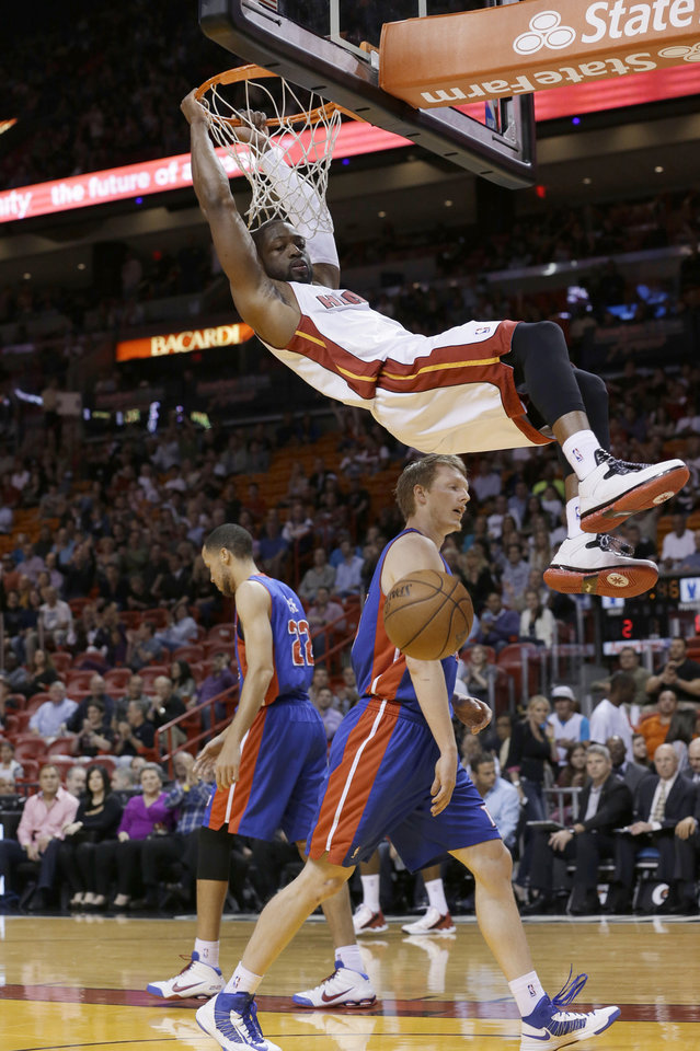Photo - Miami Heat guard Dwyane Wade hangs from the rim after a dunk, near Detroit Pistons forward Kyle Singler, center, and forward Tayshaun Prince, rear, during the first half of an NBA basketball game, Friday, Jan. 25, 2013, in Miami. (AP Photo/Wilfredo Lee)