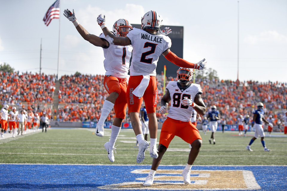 Photo - Oklahoma State's Tylan Wallace (2) celebrates his touchdown with Landon Wolf (1) and Jelani Woods (89) during a college football game between the Oklahoma State University Cowboys (OSU) and the University of Tulsa Golden Hurricane (TU) at H.A. Chapman Stadium in Tulsa, Okla., Saturday, Sept. 14, 2019. [Sarah Phipps/The Oklahoman]