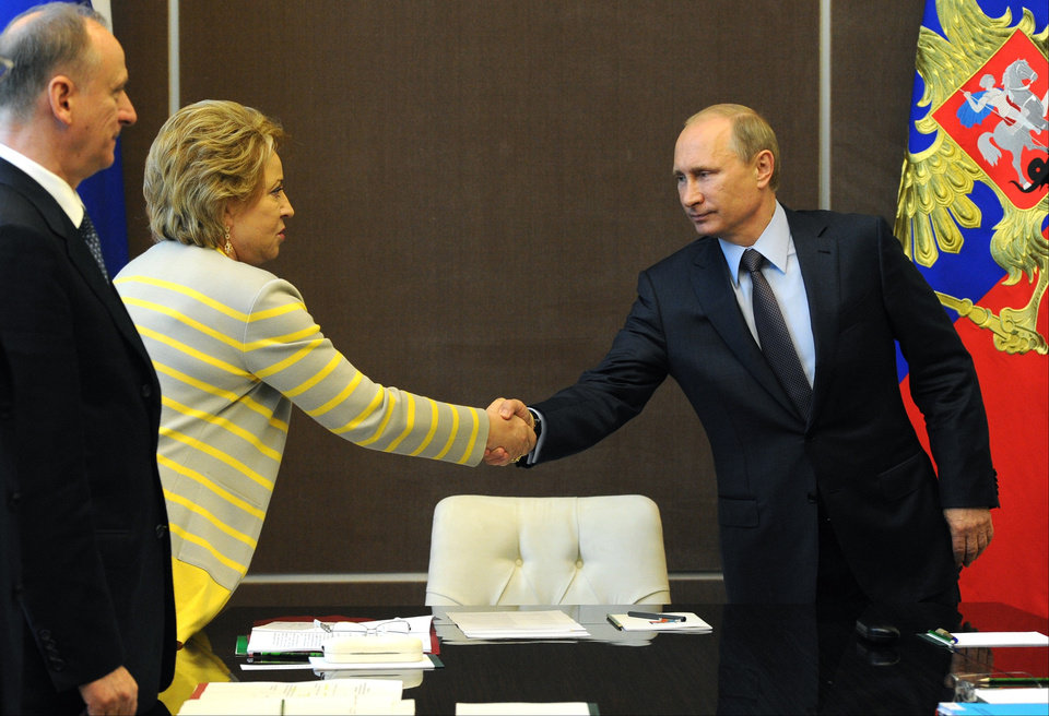 Russian President Vladimir Putin shakes hands with upper parliament chamber speaker Valentina Matviyenko prior to the Security Council meeting in the Russian Black Sea resort of Sochi on Monday, May 19, 2014. Russian President Vladimir Putin has ordered troops deployed in regions near Ukraine to return to their home bases, the Kremlin said Monday. (AP Photo/RIA Novosti Kremlin, Mikhail Klimentyev, Presidential Press Service)