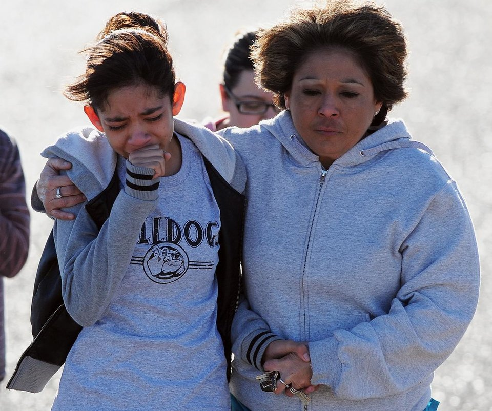 Photo - A student, left, is hugged following a shooting at Berrendo Middle School, Tuesday, Jan. 14, 2014, in Roswell, N.M. A shooter opened fire at the middle school, injuring at least two students before being taken into custody. Roswell police said the school was placed on lockdown, and the suspected shooter was arrested. (AP Photo/Roswell Daily Record, Mark Wilson)