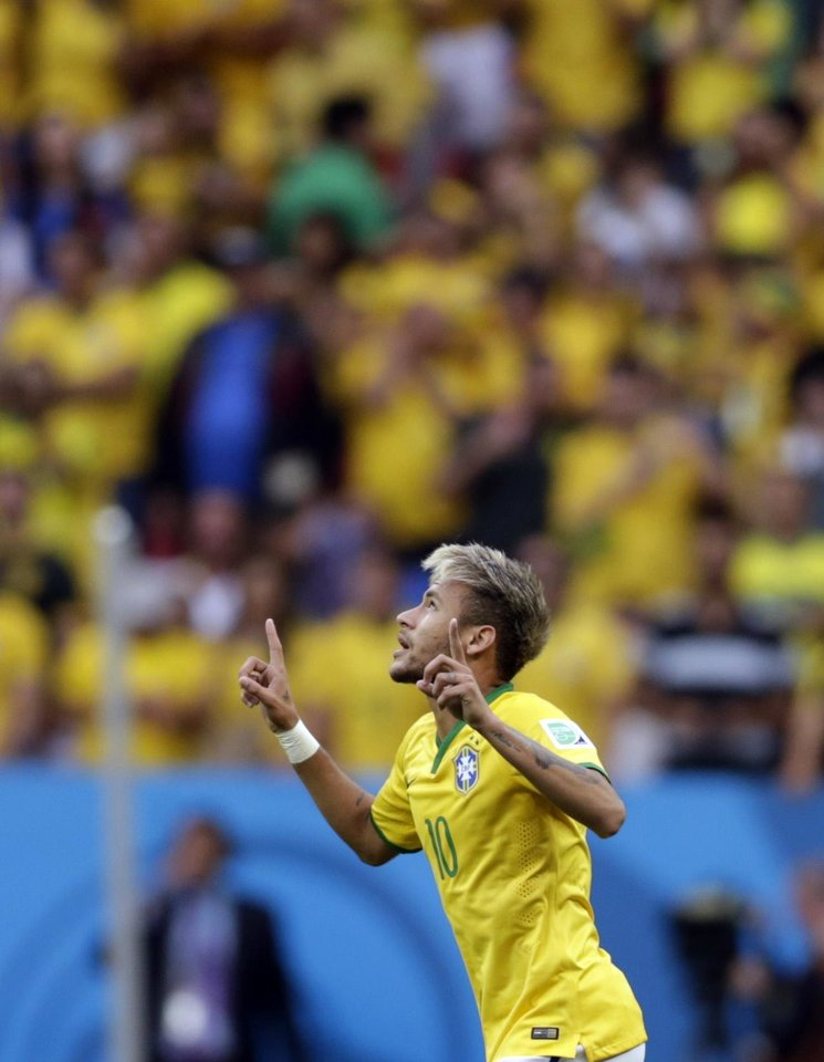 Photo - Brazil's Neymar celebrates scoring the opening goal during the group A World Cup soccer match between Cameroon and Brazil at the Estadio Nacional in Brasilia, Brazil, Monday, June 23, 2014. (AP Photo/Dolores Ochoa)